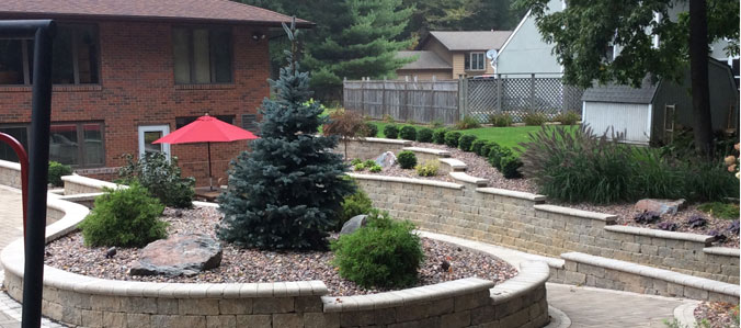 hardscaped back patio with shrubs and umbrellas