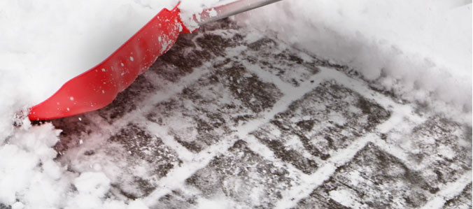 snow and ice removal with red shovel
