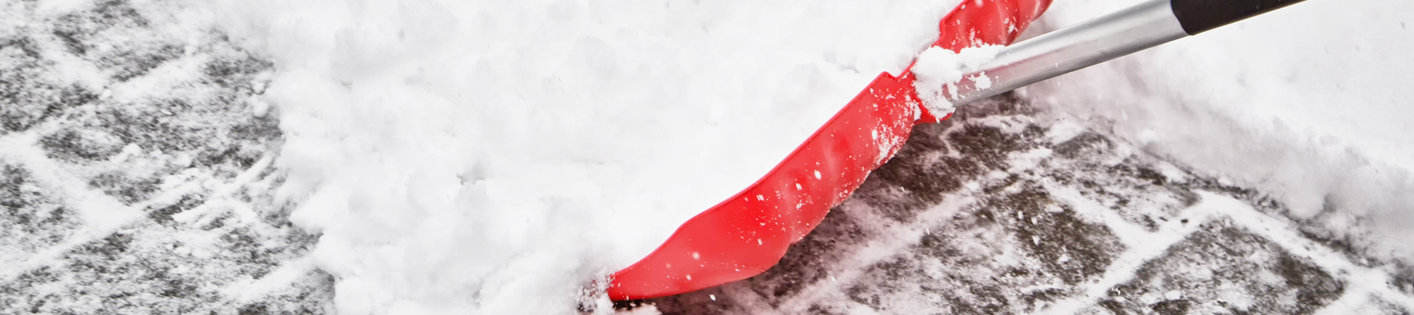 snow shoveling with red shovel on sidewalk